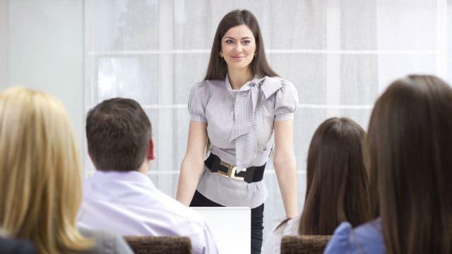 female teacher teaching infront of her students